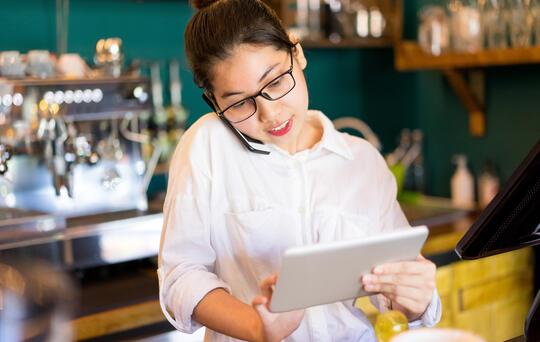 waitress looking at tablet - increase restaurant bookings