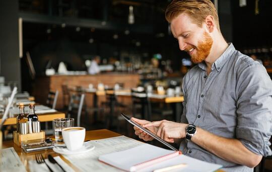 man som tittar på en iPad på en restaurang