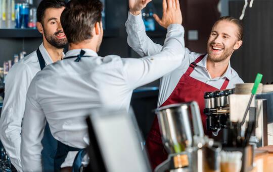 contratar a empleados camareros chocando palmas en restaurante