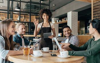 Kellnerin begrüßt Kunden - Restaurantmanagement
