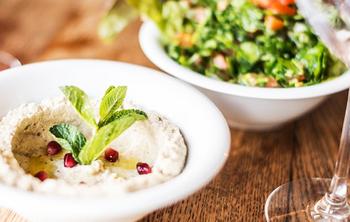 ElTenedor - Atraer clientes con platos vegetarianos en el restaurante. Plato de hummus y verduras