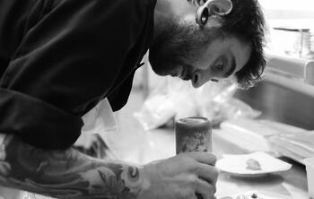 Para captar clientes, los restaurantes rotan sus chefs. En la imagen, un Chef con tatuajes sirve un plato