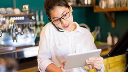 serveerster die naar tablet kijkt - restaurantreservaties verhogen