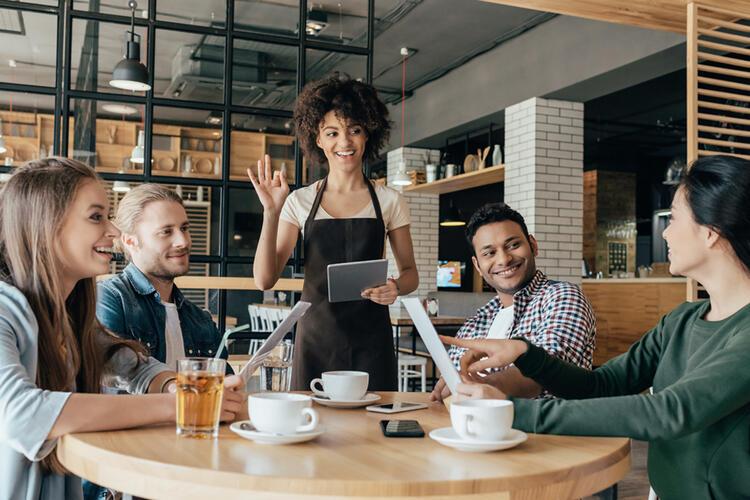 Une  serveuse accueillant des clients – gestion de restaurant