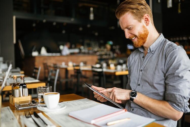 man looking a an iPad in a restaurant